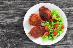 Зажаренные бедренные кости цыпленка с свежим салатом, осматривают сверху Стоковое Фото