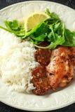 Зажаренные в духовке бескостные skinless бедренные кости цыпленка с рисом и зеленым смешиванием салата овоща стоковое фото