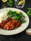 Зажаренные в духовке бескостные skinless бедренные кости цыпленка с рисом и зелеными овощами смешивают стоковые фото