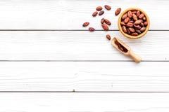Зажаренные в духовке бобы кака на белом деревянном космосе экземпляра взгляд сверху предпосылки Сырье для бурого пороха Африканец Стоковое Изображение RF