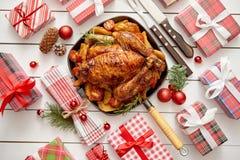 Зажаренные в духовке весь цыпленок или индюк служили в лотке утюга с украшением рождества стоковое фото