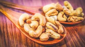 Зажаренные в духовке гайки анакардии на деревянной ложке Roasted посолило гайки анакардии на белой предпосылке Здоровая еда, анак Стоковая Фотография