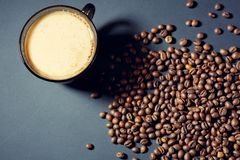 Зажаренные в духовке зерна и чашка ароматичного кофе на таблице в темном образе стоковое фото rf