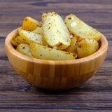 Зажаренные в духовке картошки с травами и солью Провансали в шаре на деревянной предпосылке Закройте вверх по взгляду стоковое изображение rf