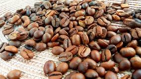 Зажаренные в духовке коричневые кофейные зерна на предпосылке ткани стоковая фотография rf