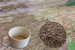 Зажаренные в духовке кофейные зерна и белая чашка кофе на старой деревянной плате Стоковые Изображения RF