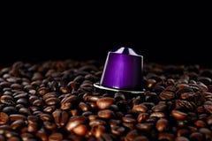 Зажаренные в духовке кофейные зерна и капсула над чернотой стоковое фото rf