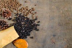 Зажаренные в духовке кофейные зерна в коричневой бумажной сумке на деревянном столе стоковое изображение rf
