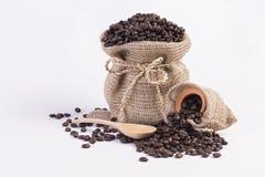 Зажаренные в духовке кофейные зерна в мешках пеньки и деревянной ложке на белой предпосылке Стоковые Фото
