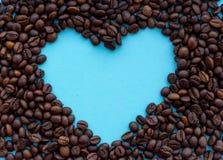 Зажаренные в духовке кофейные зерна с открытым пространством сердца в середине на голубой предпосылке Концепция питья ароматности Стоковые Фото