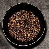 Зажаренные в духовке кофейные зерна в черной чашке на предпосылке darck Стоковая Фотография