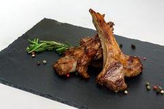 Зажаренные в духовке нервюры овечки с розмариновым маслом и перцем на черной плите Стоковое Изображение RF