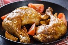 Зажаренные в духовке ноги цыпленк цыпленка с клин и томатами картошки Стоковое Фото