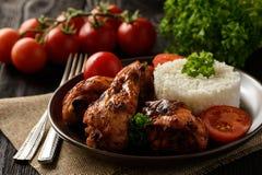 Зажаренные в духовке ноги цыпленк цыпленка с томатами и кипеть рисом стоковое фото rf