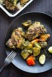Зажаренные в духовке бедренные кости и картошки цыпленка чилей cilantro в черном лотке Стоковое фото RF