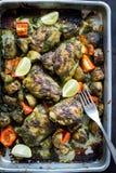 Зажаренные в духовке бедренные кости и картошки цыпленка чилей cilantro в черном лотке Стоковое Изображение