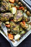 Зажаренные в духовке бедренные кости и картошки цыпленка чилей cilantro в черном лотке Стоковые Изображения RF