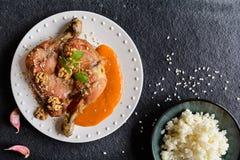 Зажаренные в духовке бедренные кости цыпленк цыпленка взбрызнутые при грецкие орехи, который служат с соусом абрикоса и рисом Стоковая Фотография