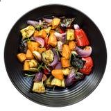 Зажаренные в духовке изолированные овощи на черном взгляд сверху диска Стоковая Фотография