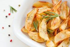 Зажаренные в духовке картошки с розмариновым маслом на белой предпосылке Стоковое Фото