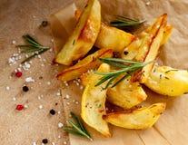 Зажаренные в духовке картошки с розмариновым маслом на деревянной предпосылке Стоковые Фото