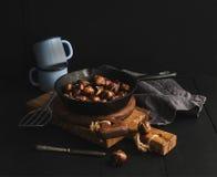 Зажаренные в духовке каштаны в skillet варя лоток над досками rusti деревянными, голубая эмаль mugs, полотенце на темной предпосы Стоковое Изображение RF