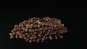Зажаренные в духовке кофейные зерна вращают на черной предпосылке сток-видео