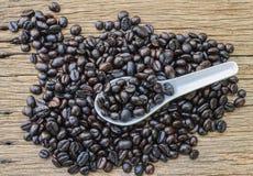 Зажаренные в духовке кофейные зерна в белой ложке Стоковая Фотография RF