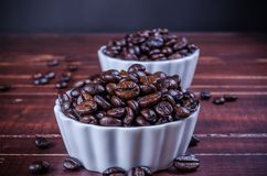 Зажаренные в духовке кофейные зерна в белом фарфоре шара на деревянном backg Стоковая Фотография