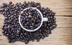 Зажаренные в духовке кофейные зерна в кофейной чашке Стоковое Изображение RF