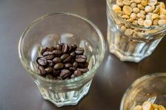 Зажаренные в духовке кофейные зерна в малом стекле Стоковые Фото