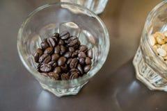 Зажаренные в духовке кофейные зерна в малом стекле Стоковое фото RF