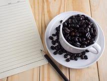 Зажаренные в духовке кофейные зерна в довольно белых чашке и памятке на деревянном столе Стоковые Изображения
