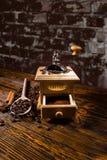 Зажаренные в духовке кофейные зерна, деревянная ложка и точильщик руки Стоковое Изображение