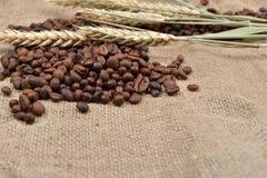 Зажаренные в духовке кофейные зерна на коричневой предпосылке джута, с несколькими thre Стоковые Фото