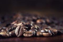 Зажаренные в духовке кофейные зерна разлили свободно на деревянном столе Стоковое Изображение RF