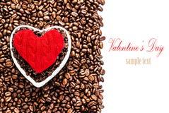Зажаренные в духовке кофейные зерна с красным сердцем над предпосылкой кофейных зерен Стоковое Изображение