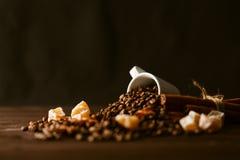 Зажаренные в духовке кофейные зерна с чашкой на предпосылке hessian джута Стоковое фото RF