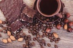 Зажаренные в духовке кофейные зерна с шоколадом и гайками на деревянной поверхности Стоковые Изображения RF
