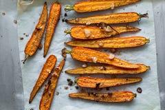 Зажаренные в духовке моркови весны на пергаменте с чесноком, горохами перца и кориандром Стоковое Фото