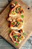 Зажаренные в духовке стейки филе Турции на разделочной доске и на деревянной таблице Очень вкусное сваренное мясо Взгляд сверху Стоковое фото RF
