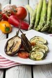 Зажаренные в духовке цукини, баклажан и болгарский перец с томатным соусом Зажаренные в духовке овощи на белой деревенской предпо стоковые фото