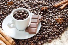 Зажаренные зерна кофе с чашкой на серебряном диске с шоколадом и печеньями в фасолях чашки кофе стоковое изображение