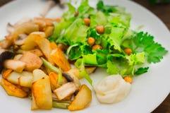 Зажаренные картошки зажарили в духовке с одичалыми грибами на белой плите и зеленом салате на предпосылке деревянного стола Дерев Стоковая Фотография RF