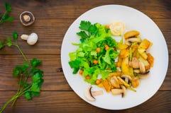 Зажаренные картошки зажарили в духовке с одичалыми грибами на белой плите и зеленом салате на предпосылке деревянного стола Дерев Стоковое Изображение