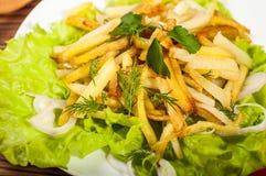 Зажаренные картошки на белой плите с травами на деревянной предпосылке взгляд сверху Стоковые Фото