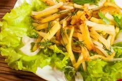 Зажаренные картошки на белой плите с травами на деревянной предпосылке взгляд сверху Стоковое фото RF
