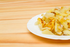 Зажаренные картошки на белой плите Стоковая Фотография