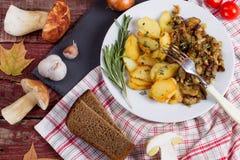 Зажаренные картошки с cepes в плите на таблице Стоковое фото RF