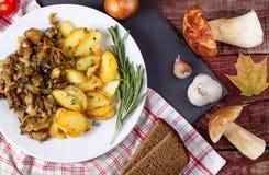 Зажаренные картошки с cepes в плите на таблице Стоковое Изображение